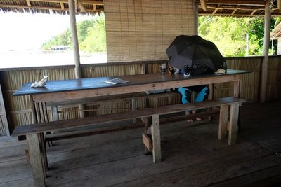 At work in the dining room, wearing his wetsuit, using an umbrella to block the sunlight, Koranu Fyak guest house, Kri island, Raja Ampat