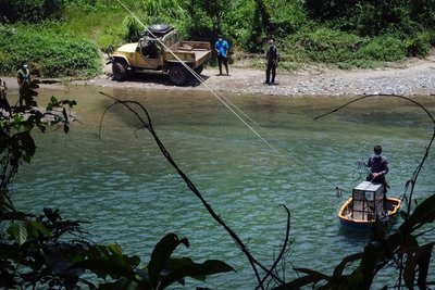 The orangutan is transported across the river and released