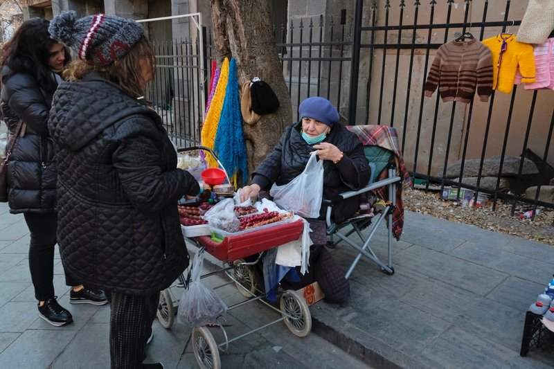 A woman selling churchkehela, traditional candle-shaped sweets, out of an old baby carriage that looks like an homage to the Odessa Steps scene in Battleship Potemkin