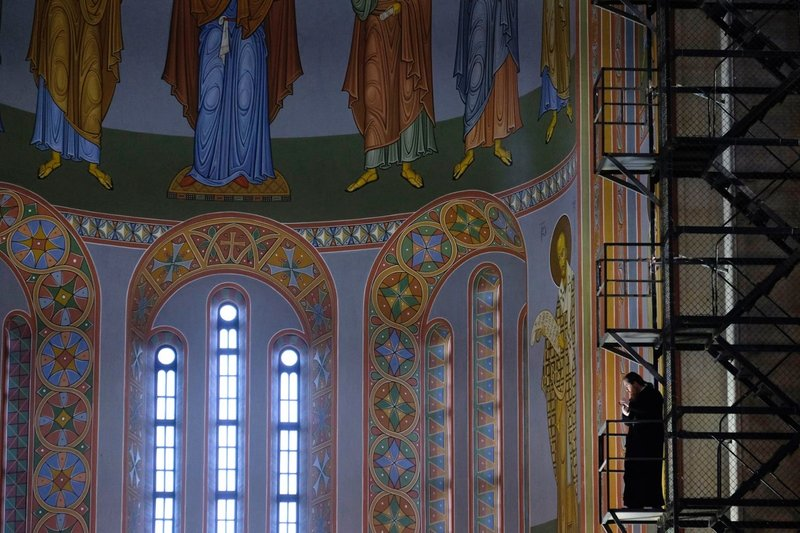 A priest standing on scaffolding in the cathedral