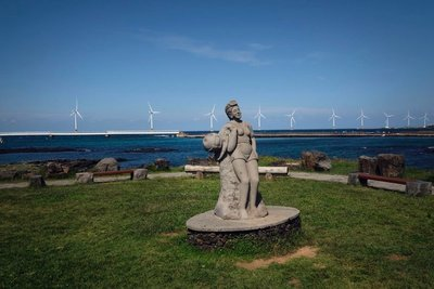 Statue of a Haenyeo with Sinchang wind far in the background