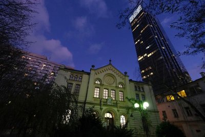 The synagogue wedged between tall, modern buildings