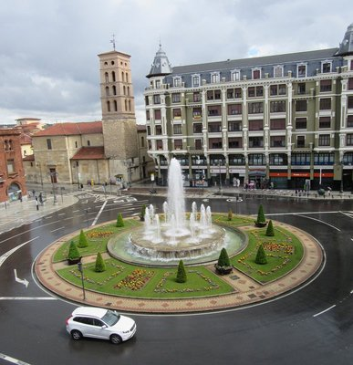 The pretty fountain in the middle of the square.  The rain is reflecting light on the street.