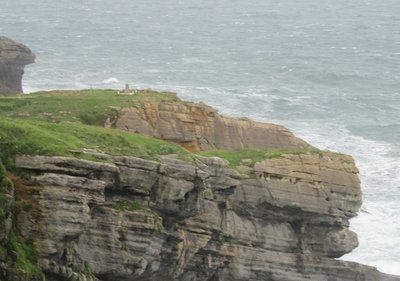 A nearby cliff with a miniature lighthouse