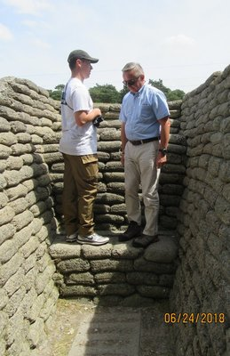 A father and son look out over a trench wall