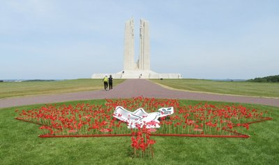 Back of the Vimy monument with paper poppies and peace dove