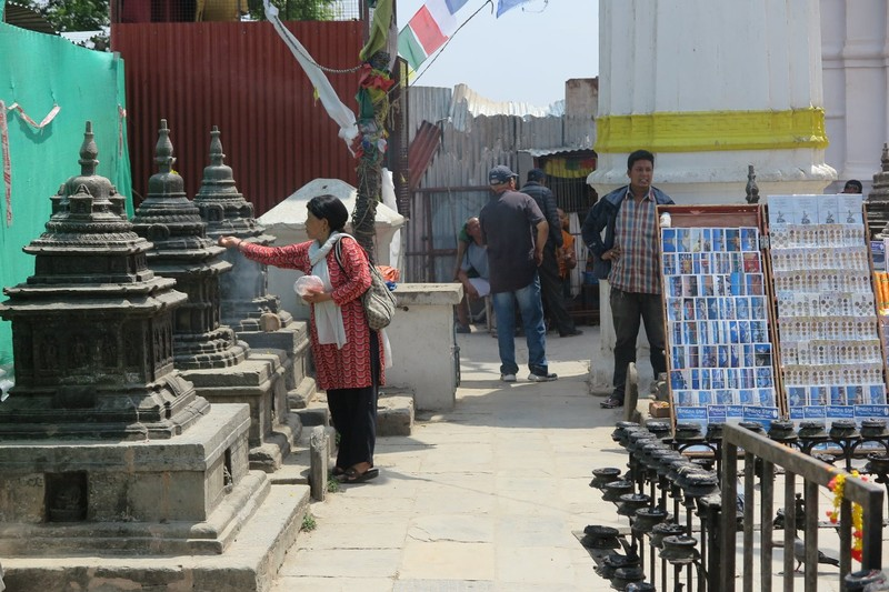 Woman sprinkling water and putting little piles of rice on Chaitya
