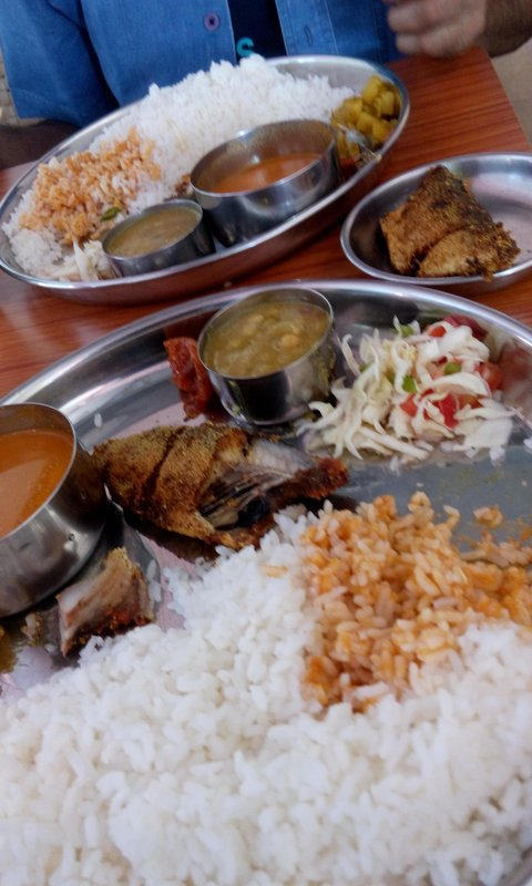 Eating delicious fish curry rice on Goa beach
