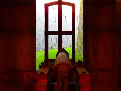 Kanonenschießscharte mit trockenem Burggraben