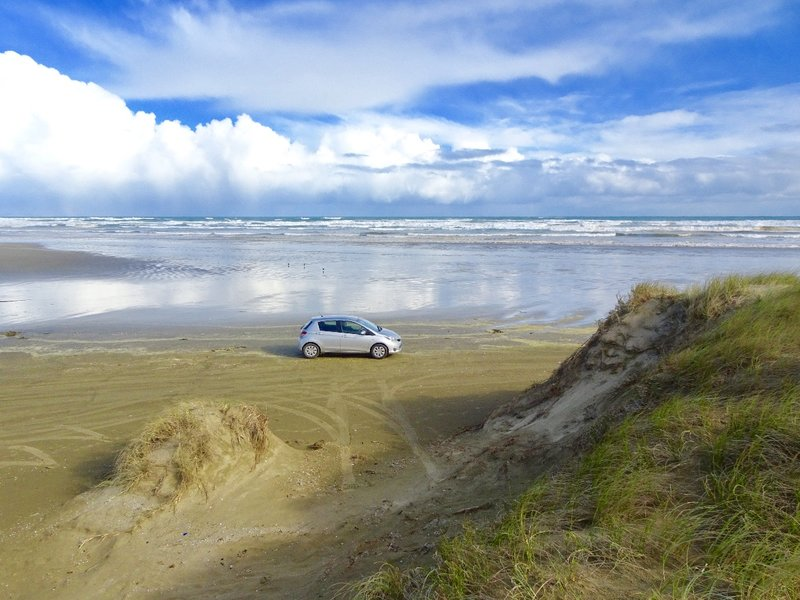 """This is our """"mean machine"""" pretending to drive on 90 Mile Beach.  If you have the right vehicle and knowledge, you can drive the whole beach."""