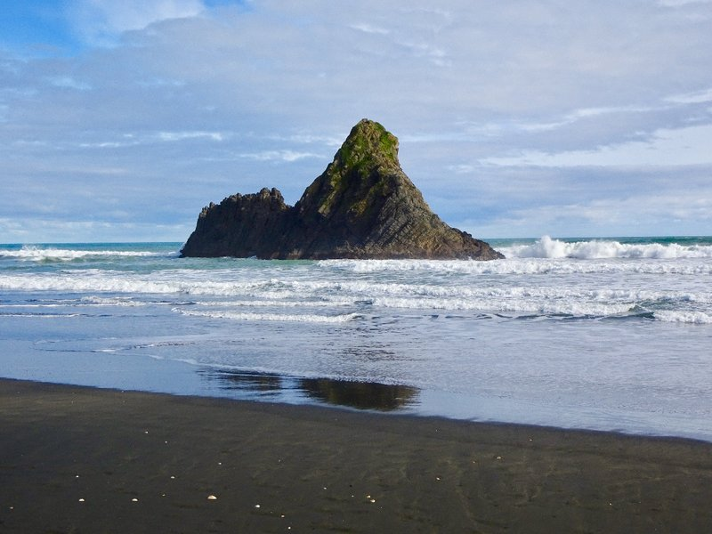 This black sand beach is called Karekare Beach. It is here that some of the scenes from the movie 'The Piano' were filmed. Holly Hunter, Anna Paquin and her piano, first landed on this beach in the film.