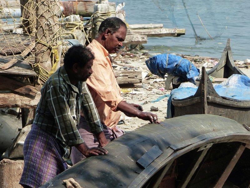 Fishermen mending their boat, Fort Cochin