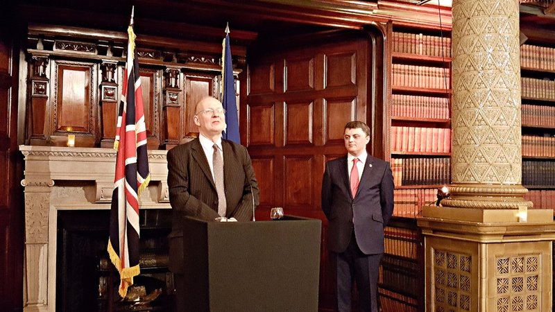Ambassador of Kosovo looks on as an important British diplomat gives a speech