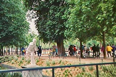 The Tuileries Gardens, see the umbrellas as everyone runs for the Metro