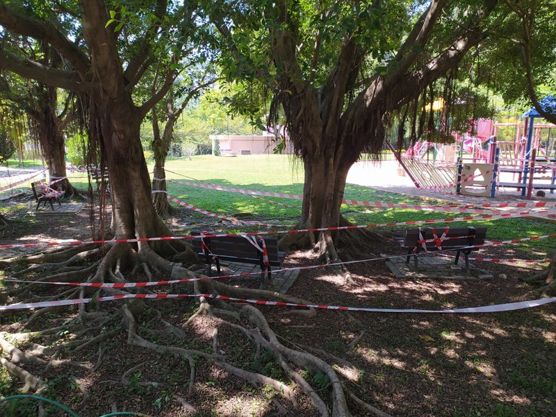 Playgrounds and seating areas are taped off.
