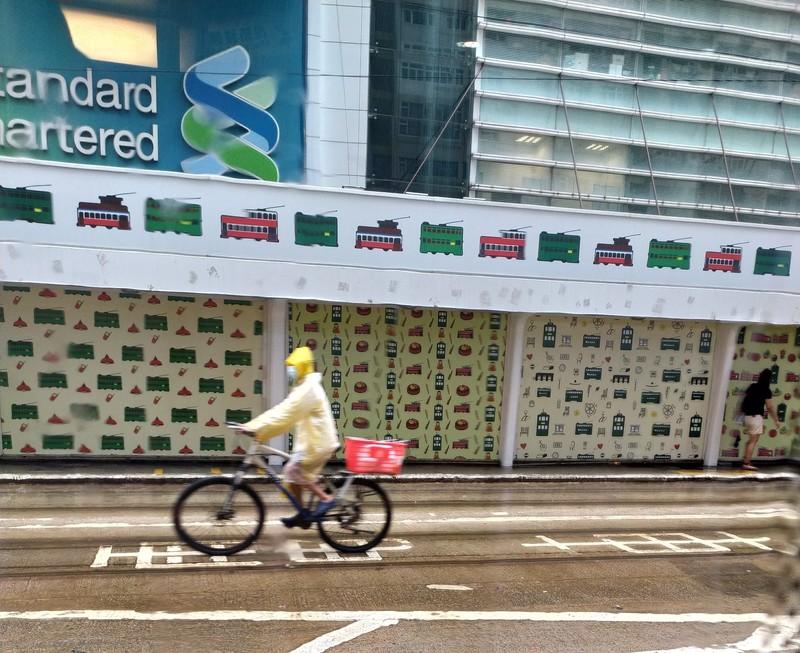 Lone cyclist battling through a red rain storm.