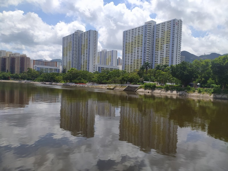 Tall buildings reflected in the Shing Mun River.
