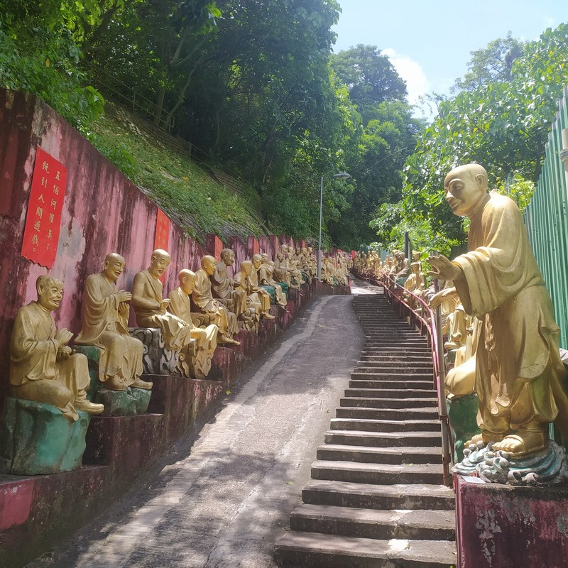 The pathway is lined with golden arhut statues.