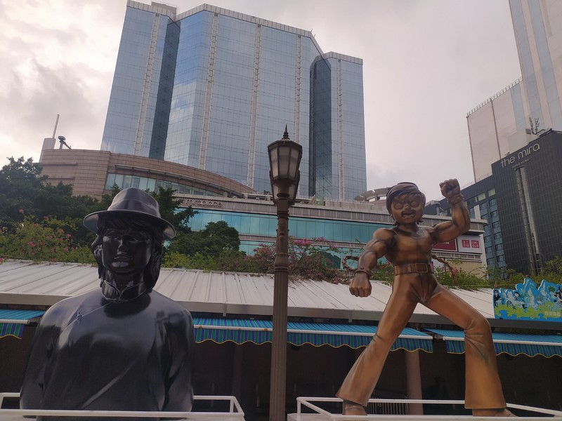 Statues with tall buildings on Nathan Road.