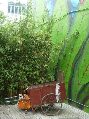 szemetes kocsi parkol a bambusz mellett