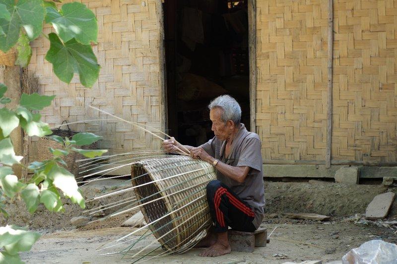 A grandfather braiding a basket