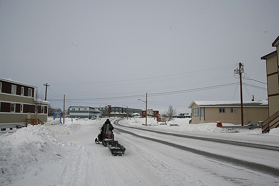 Guy snowmobiling on the road