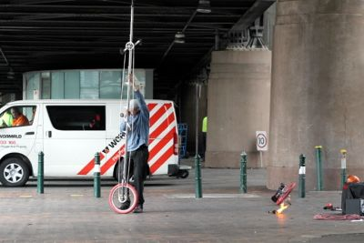 Fire juggling man getting ready to mount his unicycle