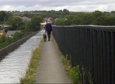 Looking back -Man and dog walking along the canal path