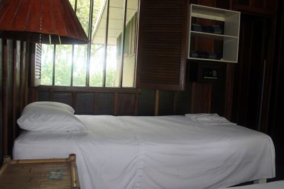 Cabin, one bed, shelf with blankets and window