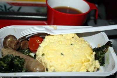 scrambled eggs on a muffin, a sausage, spinach and mushrooms with a cherry tomato