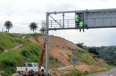 Workers on a highway sign above the highway