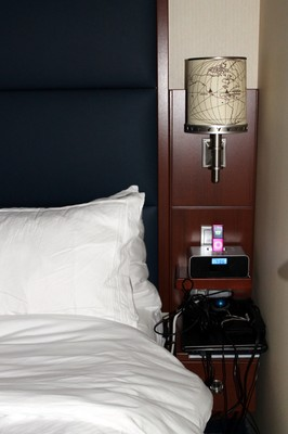 My bed with the Navigator plan of the day on it and Granddaughter charging her device on the clock radio