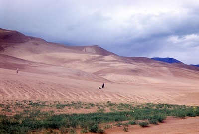 Sand dunes with tiny people on the top