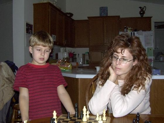 Grandson playing chess with his mother