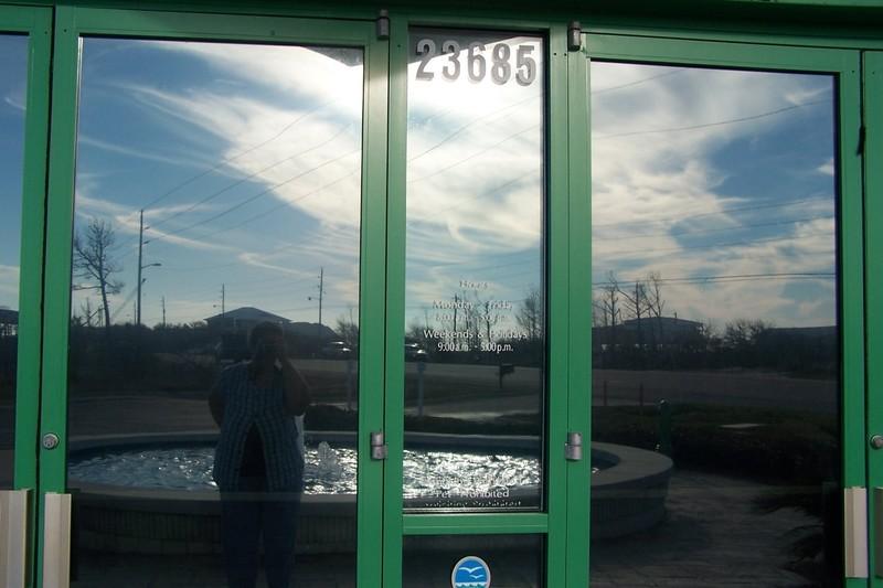 Reflections in the door of the Orange Beach Welcome Center