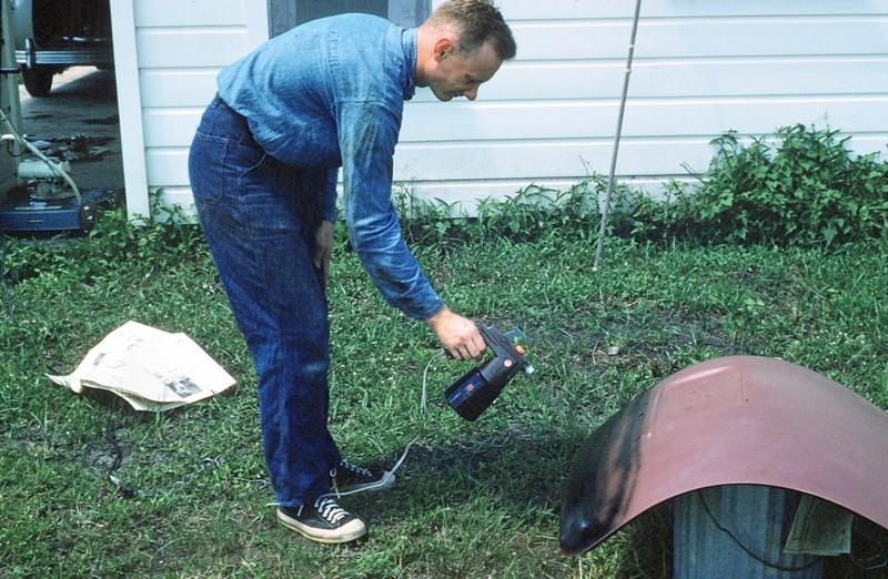Bob painting a trunk lid - the power mower that we had to buy behind him on the left