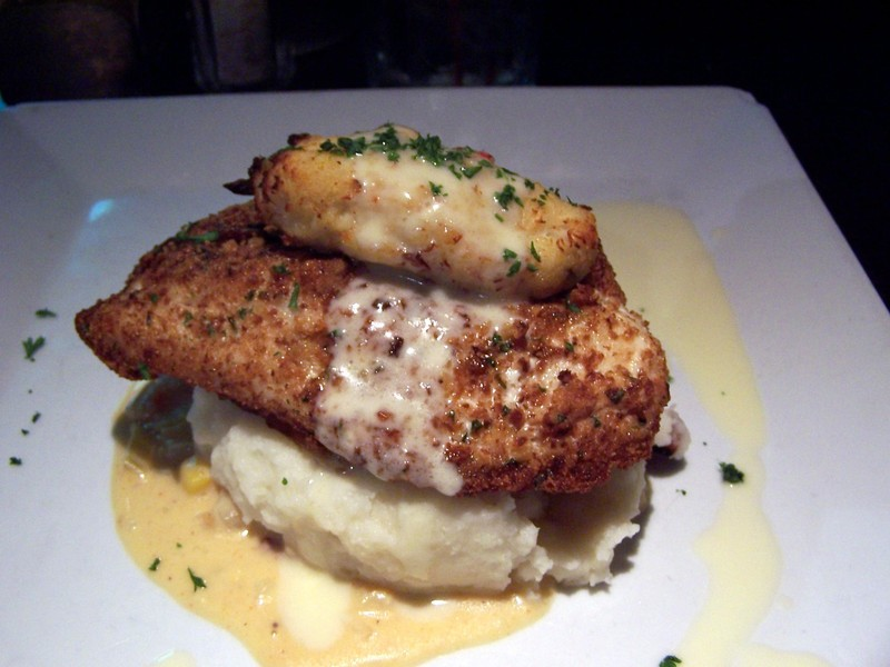 Fish served on top of mashed potatoes with a piece of chicken on top