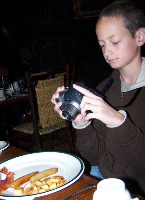 Taking a picture of his breakfast