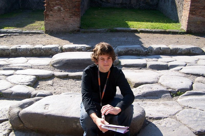 My grandson sitting on a step stone in Pompeii with the site map