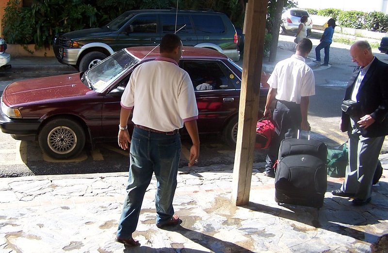 Bob helping the driver unload the luggage into his maroon sedan at the hotel