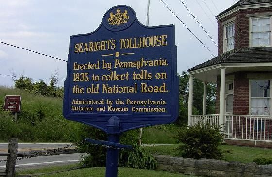 Sign with toll house behind it