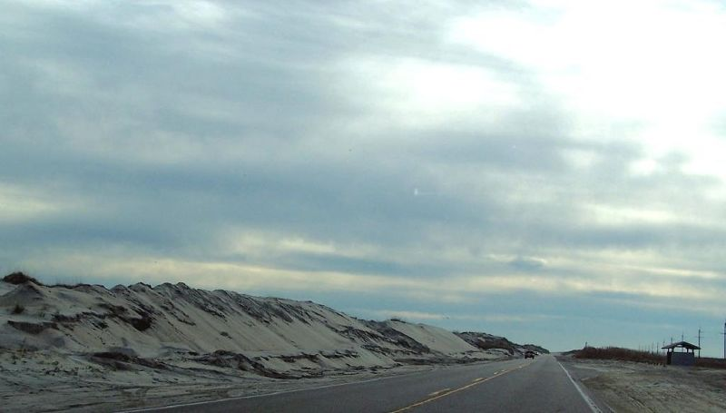 Road flanked by sand dunes