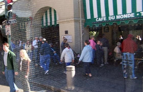 Reflection of bus seat back in window as we pass Cafe du Monde