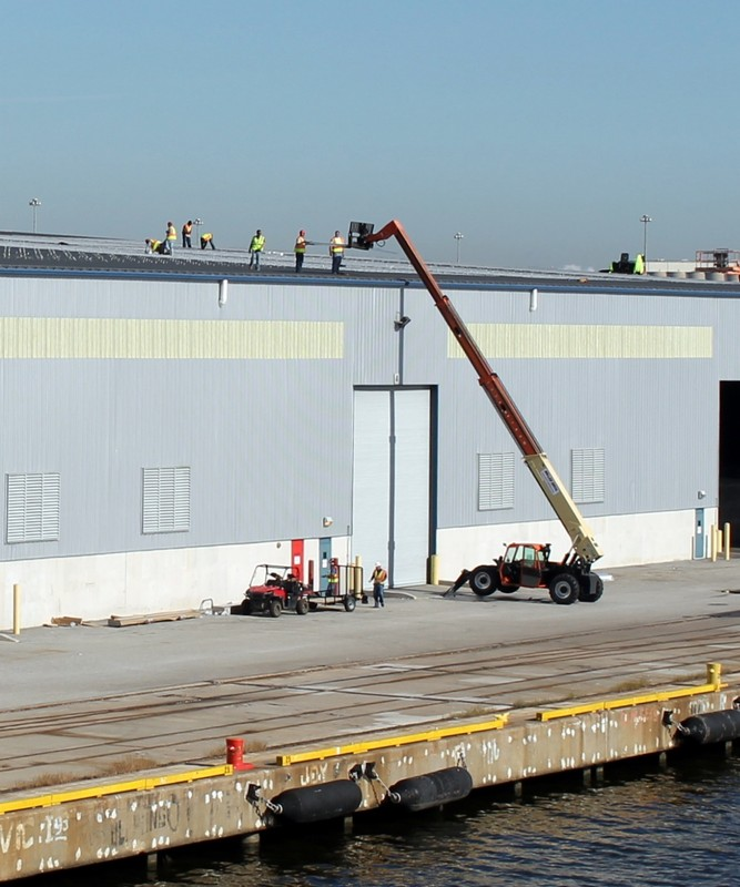 Roofing workers on adjoining warehouse