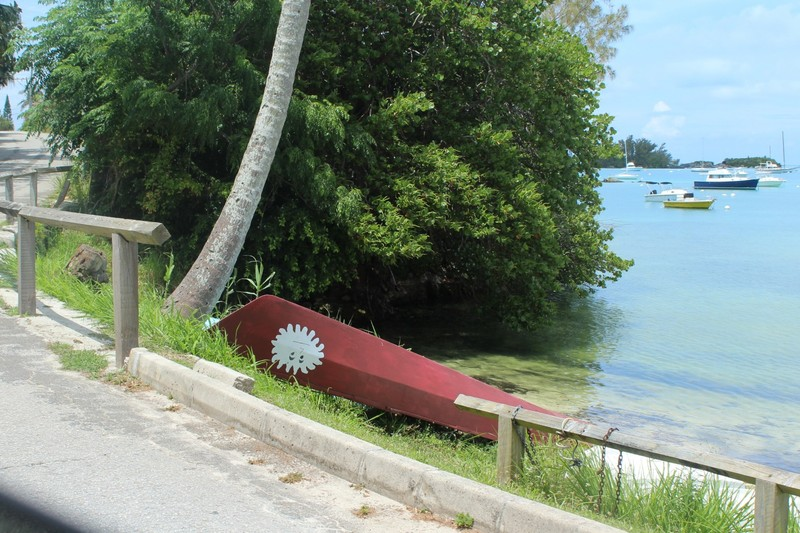 Boat pulled up on shore with sun graphic on the bow (upside down)