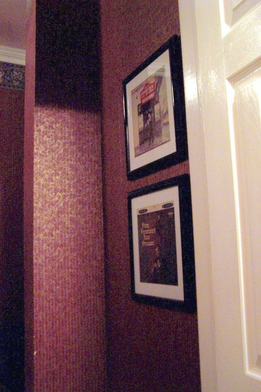 Pictures on the wall, wallpaper with a border next to the bathroom door