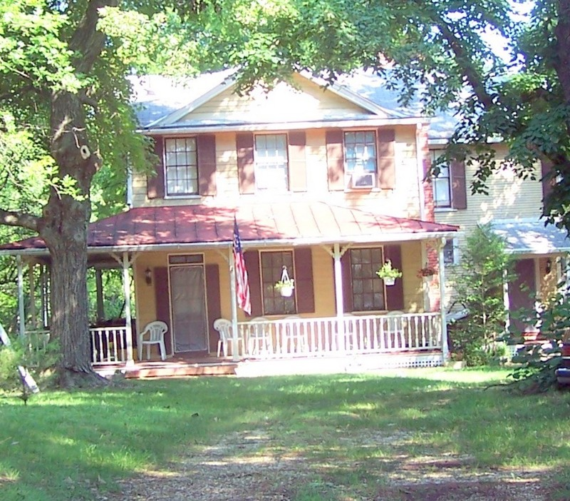 Our house in the summer.  Maple tree on the left and window A/C