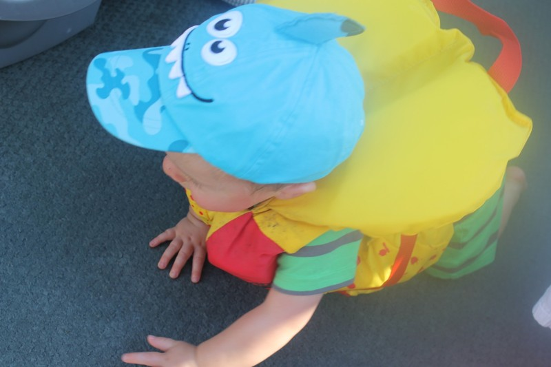 Great grandson crawling on the pontoon boat floor