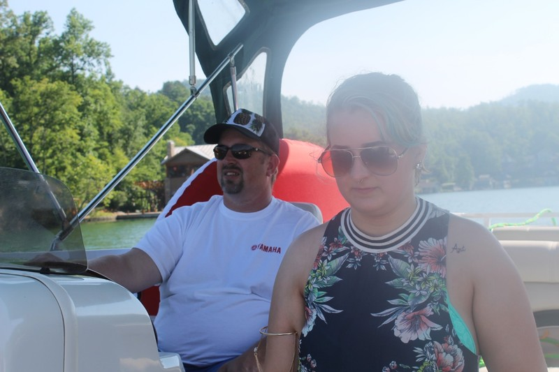 Son at the helm of the boat and granddaughter