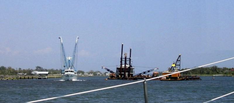 Shrimp boat passing barge with dredge